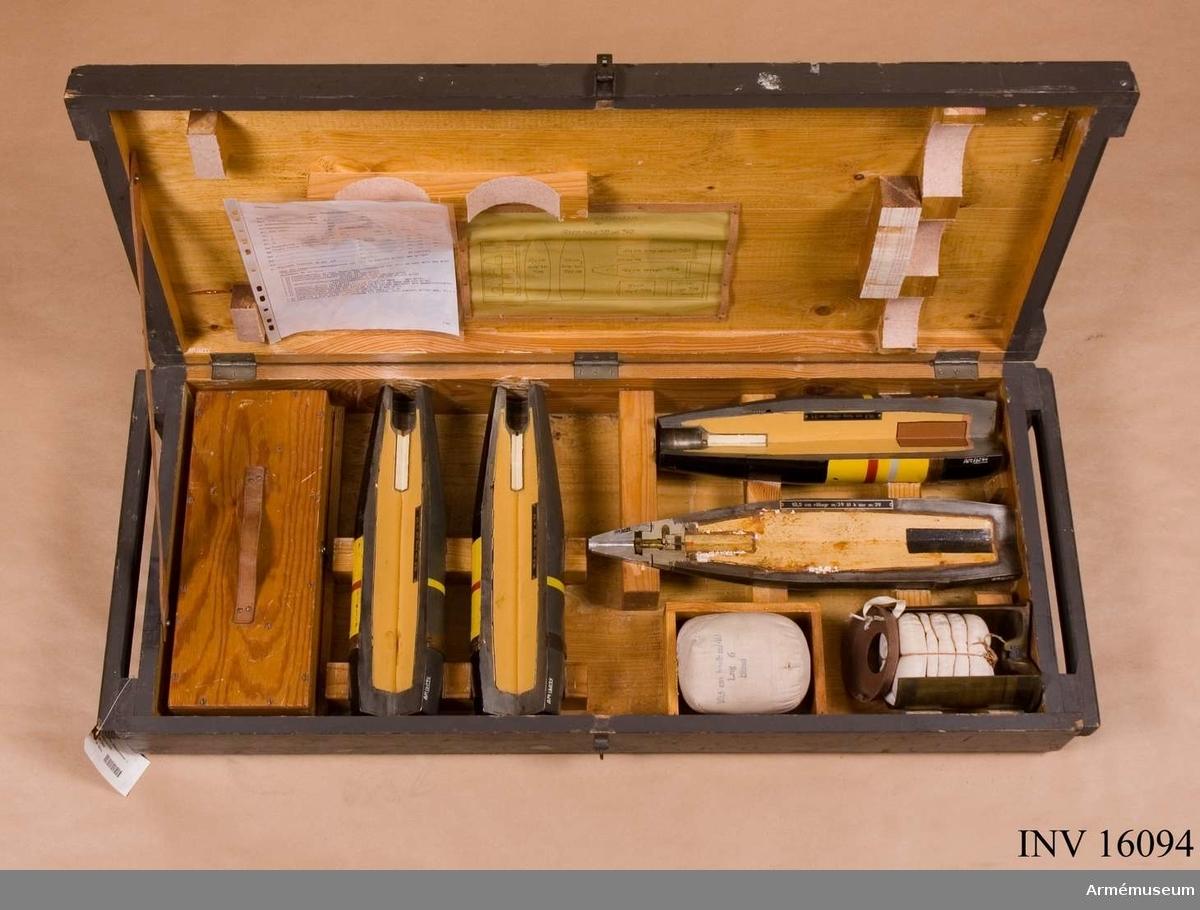 Låda för demonstrationsammunition för 10.5 om haubits m/1939 och 1940. Genomskuret. Bestående av 13 delar. 1 st förvaringslåda av trä. Märkt: Demonstrationsam för 10.5 cm hanb m/39 och m/40. 1 st förvaringslåda för tändrör av trä, 1 st fördrjtsspetsanslagrör m/1922 (f sar m/22), 1 st fördrjtsspetsanslagrör m/1934 ( f sar m/34), 1 st ögonblickligkänsligspetsanslagsrör m/1934 (ök stidar  m/34), 1 st ögonblickligkänsligspetstidanslagsrör m/1934 (ök stidar m/34), 1 st detonator m/1922 (det m/22), 2 st tungspränggranat m/1934 kal 10.5 cm (10.5 cm tung sgr  m/34), 1 st tungrökspränggranat m/1934 kal. 10,5 cm (10,5 cm sgr m/39 med ögonblickligt fördröjt känsligt spetsanslagsrör m/1939 (öf k sar m/39), 1 st laddning 6 (lng 6) till haubits m/1940 kal 10,5 cm, 1 st laddningshylsa m/1939 med laddning 1-5 m/1939, till haubits m/1940 kal 10.5 cm.