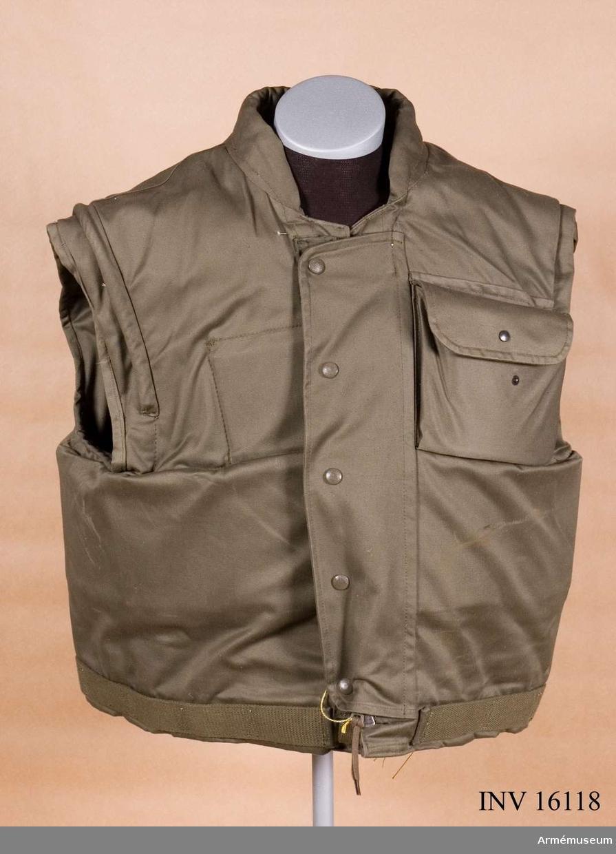 Modell / Bundeswehr. Av grågrönt bomullstyg s k varpsatin. Har blixtlås och knäppning framtill. Innandöme av skottsäker plåt.