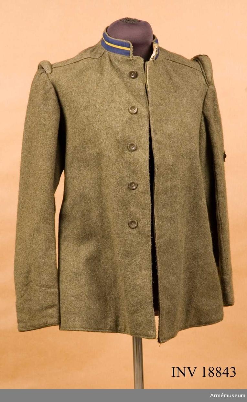 """Grupp C I. För officer vid 81 och 82 infanterireg:t, Brigade Torino. Av grön-grått kläde, 64 cm lång. Enradig med 5 khakifärgade knappar, som knäppes inuti. På rockens baksida 2 inskärningar, som knäppes varje knäpps inuti med 2 knappar. På båda axlarna vid ärmsömmarna finns två avlånga kuddar  vadderade för att bättre hålla gevärsremmen på axlarna. På varje kudde ett fastsytt svart band med vitt kompaninummer """"1"""" (första kompani). Foder av vitt tyg med två inre sidofickor och den ena (mindre-med knapp) för första hjälpen (sanitets-  paket). På fodret finns stämplar """"5"""" - andra oläsligt, 4 st """"Fanteria."""" Knappar kakifärgade av ben: 5 st på bröstet och 4 st på baksidan vid inskärningarna: Krage upprättstående av samma kakikläde. På kragens båda sidor finns fastsydd """"spiegel"""" av blå-gul silkesband med små knappar av vit metall.  Blå band med gult band i mitten - känneteckensfärg för Torino-  brigaden (Infanteriregementen N 81 och N 82). Kragen knäppes med två hyskor och hakar. Ärmuppslag av samma kakikläde i vinkelform. På vänstra över- ärmen, fastsydd en bit kläde med broderade automatgevär i svart färgkännetecken för soldaten,att han tillhör maskin- gevärsavdelning. LITT  Handbuch der Uniformkunde, prof. Rickard Knötel, Hamburg 1937. Sida 234, 235. Redan år 1908 provades kakifärgad uniformer i italienska armén, under världskriget år 1915 in- fördes kakiuniform i form av en fältblus (vapenrock) med ärm- uppslag i vinkelform och uppstående krage med olika färgade silkesband på kragen (brigaden känneteckensfärger). Brigaden  Torino har """"spiegel"""" av blå silkesband med gul rand i mitten. Till torinobrigaden hör infanteriregementen N 81 och N 82. Armeen Album II. Die grauen Felduniformen der Italienischen Armée. Verlag M Ruhl, Leipzig. Sida 78. Infanterie, Felduniform Vapenrock av kakifärgat kläde (utan knappar). På kragen färgad spegel (för varje brigad olika färger). Bilaga: """"Die Unterscheidungsfarben der infanterie Brigadens (färgen på kragen). Brigade Torino (81 och 8"""