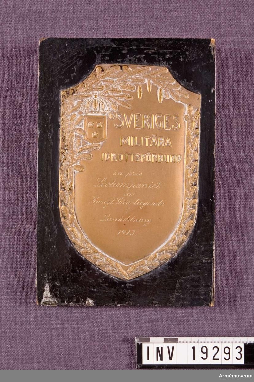 """Plakett i brons med text: """"SVERIGES MILITÄRA IDROTTSFÖRBUND 1:a pris Livkompaniet av Kungliga Göta livgarde i Livraddnimg 1913"""". Plaketten fästad på en svart lackad träplatta."""