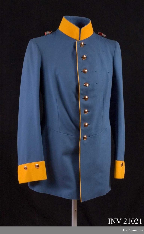 """Grupp C I. Ur uniform för överste vid Dragonreg:t König Friedrich III (2 schlesiska), nr 8 VI Armékåren, Tyskland. Består av syrtut, vapenrock, ridbyxa, långbyxa, överrock, hjälm, mössa, skärp, kartusch, bandolär, axelklaffar, sabel  med balja och portepé. Vapenrock av ljusblått kläde, Åtsittande, med midjesöm. Enradig med 8 knappar. På bakfickorna ett tvåuddigt lock med 3 knappar. Epålettslejf, b:20 mm, av galon med citrongult underkläde. Bredvid slejfen finns en fastsydd knapp. Foder av beige siden med en ficka på bröstet; bälte av samma tyg med hyska och hake. På bakre sidan finns också en ficka (inuti). Knappar silverfärgade, d:20 mm. På bröstet fickor och ärmuppslag av större modell, på axlarna  mindre. På baksidan står det """"Hochfeinew Qualität"""". Krage, upprättstående, med raka vinklar av citrongult kläde med ljusblå passpoil på överkanten. Kragen är försedd med 3 hyskor och hakar samt fodrad med ljusblått tyg.  Passpoiler citrongul, längs rockens kant och de bakre fickornas lock. Ärmuppslag (svensk modell) rakskurna av citrongult kläde med två knappar. LITT  Enl. H Knötel, Das Deutsche Heer, Zweiter Band. Kavalle- rie. Bild: 79. Regementsuniformer i färg. Das Deutsche Reichsheer, G Krickel. Sida 80, 81. Reg:t, vars färg är citrongul, grundades efter en dagorder av den 10 maj 1860. Namnchiffret """"F.R.III"""" infördes på epåletter och är av förgylld metall (nya prover), efter en dagorder av den 25 februari 1889 (fig.385.)  Vapenrocken infördes, för dragoner av blått (kornblumenblau) kläde, efter en dagorder av den 16 juni 1842. Uniformenkunde Das Deutsche Heer. H Knötel. 1935-37. Band 4.S 100. Officerare. Vapenrockens klädesfärg blev """"kornblumenblau"""" men den blev så ljus att den snarare blev """"Hellblau"""" (endast för officerarnas vapenrockar). Bekleidungsvorschrift für Offiziere und Sanitätsoffiziere des König Preuss. Heeres. Berlin 1899. Sida 52 par. 65 - vapen- rock och sida 83 par. 97 - epåletter. Beskrivning och mått. Geschichte der Bekleidung und Ausrüstung der Kö"""