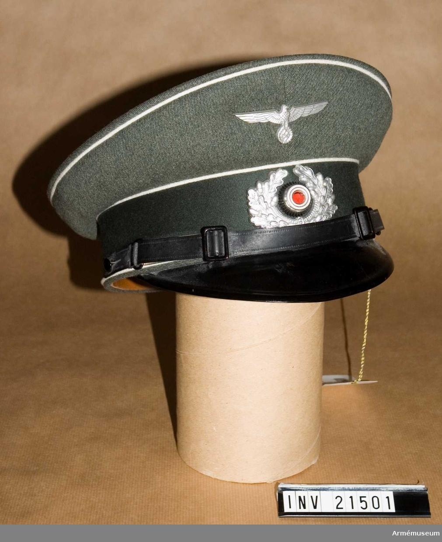 Grupp C I. Ur uniform för manskap vid infanteri i Tyskland. Består av vapenrock, ridbyxor, långbyxor, lägermössa, skärmmössa, kappa, regnkragen, ylletröja. Av fältgrått kläde. Har ett bräm, b:50 mm, ovh vit passpoal på båda kanterna samt i kullens övre kant. Foder av brunt tyg och svettrem-skärm av svart lackerat läder. Baksidan målad med brun färg.
