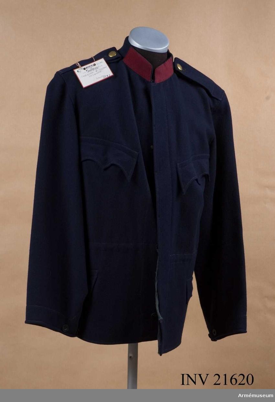 Vapenrock (blus m/1868-87), menig, Österrike. Grupp C I. Av blått. Enradig med 6 knappar och gylfknäppning. Axelklaffar av samma tyg, b:55 mm. Två sidofickor och två bröstfickor med tre-uddiga lock. Foder saknas. Krage upprättstående av kläde. På kragen finns två klaffar av rött kläde. Ärmuppslag har ett sprund med knappar.