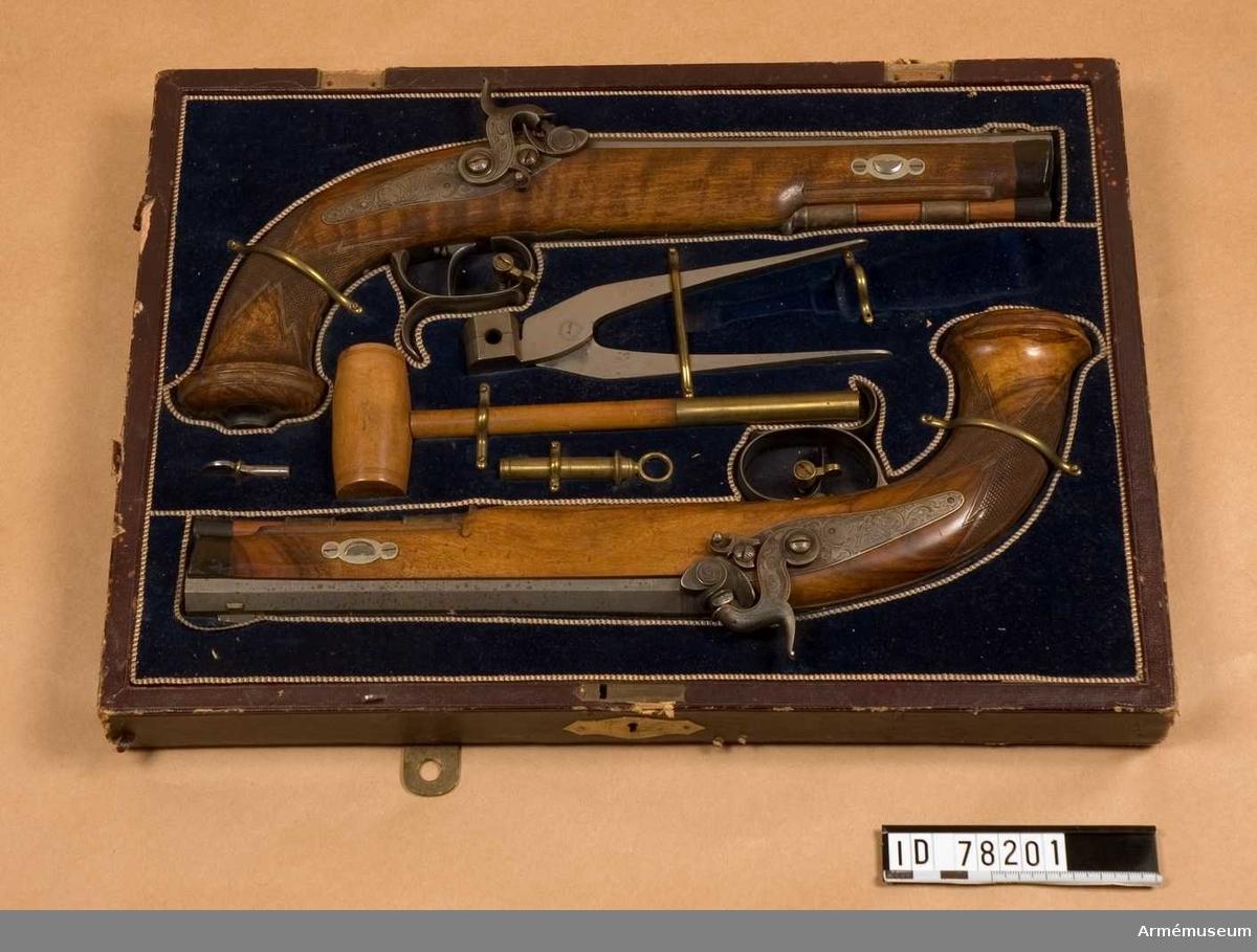 Grupp E III.  Pistolen är räfflad med slaglås och damaskerad pipa.  Åtta räfflor. På kammarstycket pipan damascherad och signerad S P Sauer & Sohn A. Suhl. Låsblecket graverat. Beslag av järn, graverat. På kolvkappan 8882. I par med 41996 och förvaras med denna jämte kulform krutmått, kulsättare, nyckel att ställa in siktet med samt nyckel att skruva ut och i knallhattstappar i en därtill avsedd låda eller schatull.  Samhörande nr är 41995-8, pistoler i par, schatull, tillbehör.