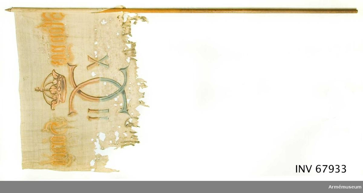 Duk: Tillverkad av enkel vit linnelärft, sydd av två horisontella våder. Nedre våden ej mätbar.   Dekor: Målad endast från dukens insida. Karl XII:s namnchiffer, dubbelt C med X-II på ömse sidor, krönt med sluten krona, i gult och brunt på den övre våden, nedre delen i svart och blått. Text på ömse sidor om chiffret, upptill i gult och nedtill i svart.   Duken fastsydd runt stången. Stång av furu.