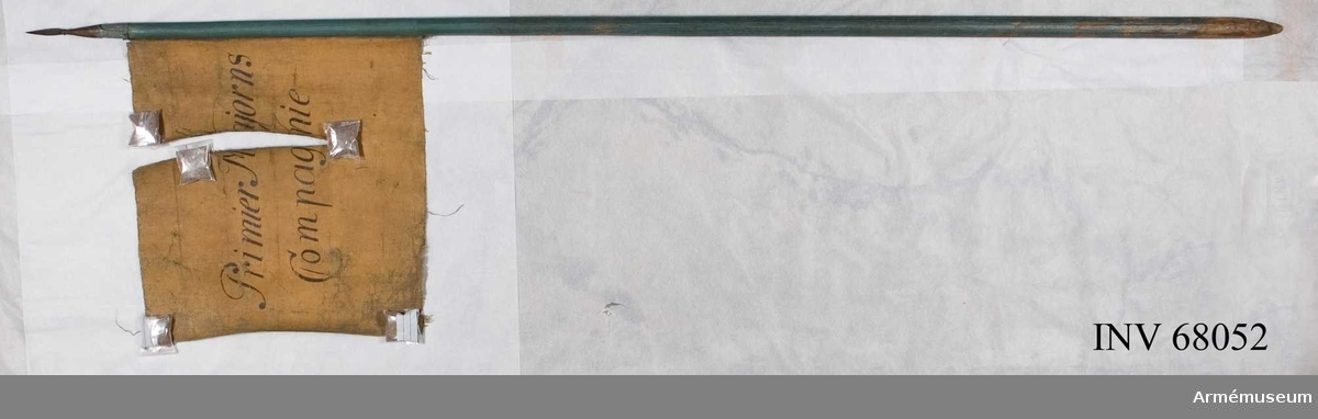 Duk: Tillverkad av enkel blå och gul lärft. Dukens vertikala ytterkant stad. Fäst med mässingsspik vid stången.  Dekor: På inre sidan målad blå med inskrift i svart på två rader.  På yttre sidan målad gul med inskrift i svart på två rader.  Stång: Tillverkad av trä, liten lansettformad. Holken i järn går ner på stången.