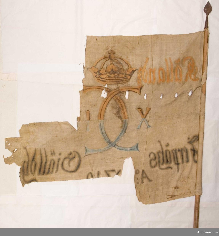 Duk: Tillverkad av enkel vit linnelärft, sammansydd av två våder.  Dekor: Målad dekor endast på dukens insida, i mitten Karl XII:s namnchiffer, med sluten krona krönt dubbelt C, på ömse sidor om detta XII i gult och brunt på den övre våden, på den nedre i blått och svart. Text på ömse sidor om namnchiffret, upptill i gult, nedtill i svar. Text nedanför namnchiffret.  Stång: Tillverkad av trä med stålspets, holk och spets i ett, spetsen är lansettformad.