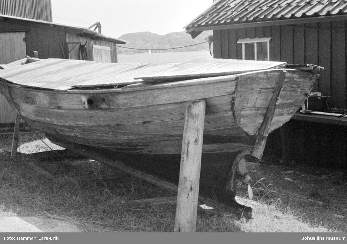 """Motivbeskrivning: """"F.d varv i Skredsvik """"bohusjulle (se Bb 17: 21). I bakgrunden till höger båtbyggarverkstaden, till vänster tillbyggnaden till virkesmagasin."""" Datum: 19800717 Riktning: S"""