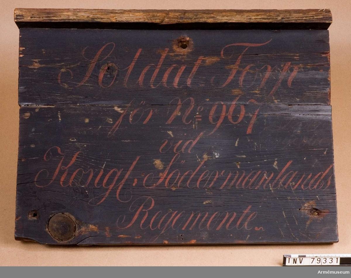Grupp L. En svartmålad rektangulär trätavla med ett smalt regnskydd. I röda bokstäver: Soldat Torp för No 967 vid Kongl. Södermanlands Regemente, på 5 rader.  967 Läggesta rote, Kärnbo socken, Gripsholms Kompani.