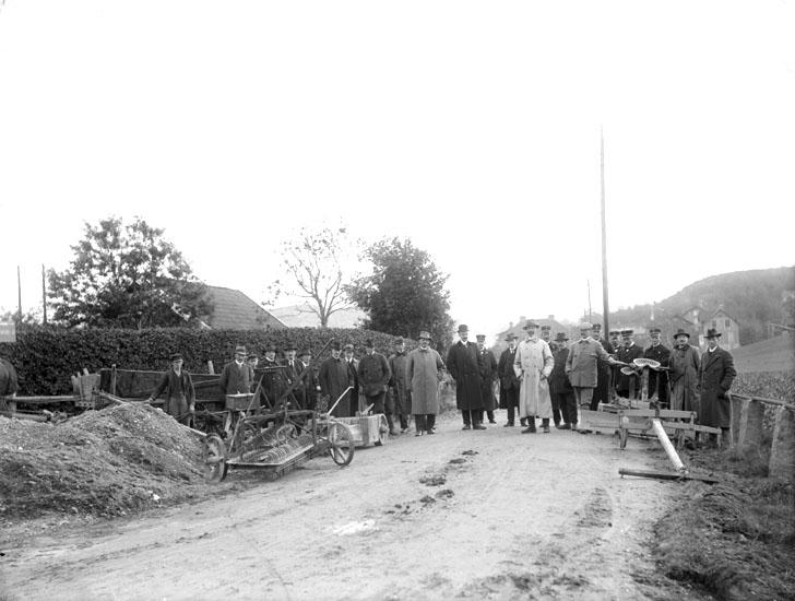 """Enligt noteringar: """"Vägbygge Stationsvägen. Husen i fonden är Munkedals järnvägsstation med tjänstebostad och till höger bebyggelse vid Jonsängen."""" (BJ)"""
