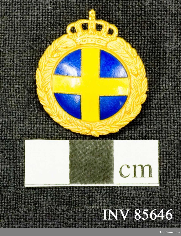 Grupp M. Åtsidan: En rund glob med landstormsmärket, omgvien av en tallkrans av förgyllt silver, vars översta ändar möta en kunglig krona.  Frånsidan: utan ornering. Mitt på baksidan- C G SPORRONG C: STOCKHOLM på 2 rader.
