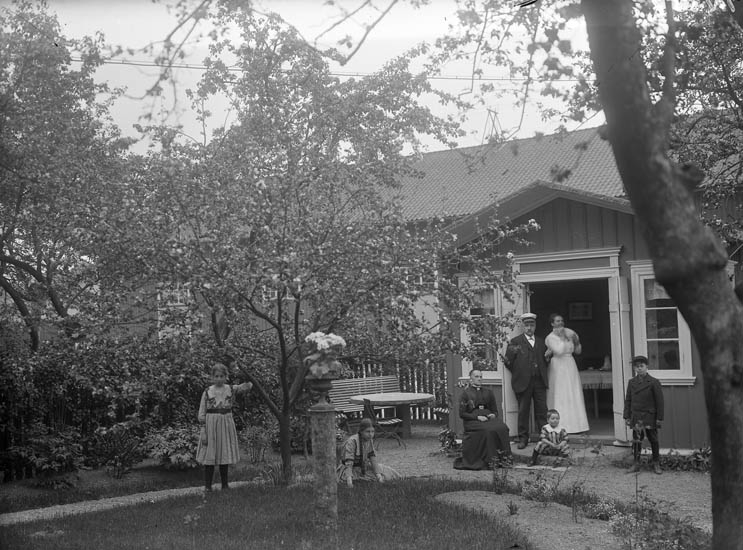"""Enligt tidigare noteringar: """"Trädgårdsidyll. Gruppfoto i trädgård framför verandaentre."""""""