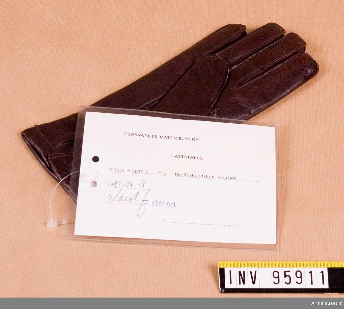 """Fodrad, femfingrad handske tillverkad av brun fårnappa och försedd med resår för åtstramning vid handloven samt slits vid överkanten. Högerhandske storlek 7. Vidhängande etikett: """"Försvarets materielverk, Fastställs, M 7331-102000-5 Befälshandskar fodrade, 1985-09-18  (oläslig underskrift)"""""""