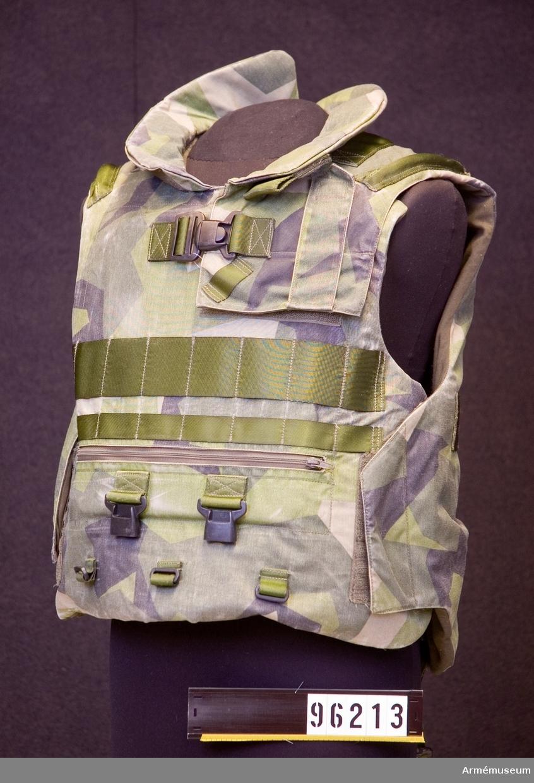 Storlek M, tillverkad 2004, yttertyg Polyamid 6.6, innertyg Polyamid 6.6, tillverkare CATO RINGSTAD AS, tillverkningsland Kina. Kroppsskyddet kan förses med underlivshölje fram och bak (AM.096166 och AM.096167)