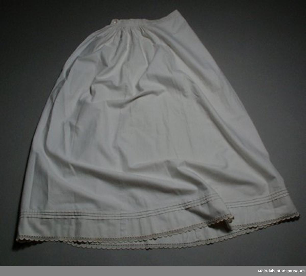 Vit, hellång underkjol med knapp och linning. Tre sydda veck nertill. Smal virkad spets i nederkant.