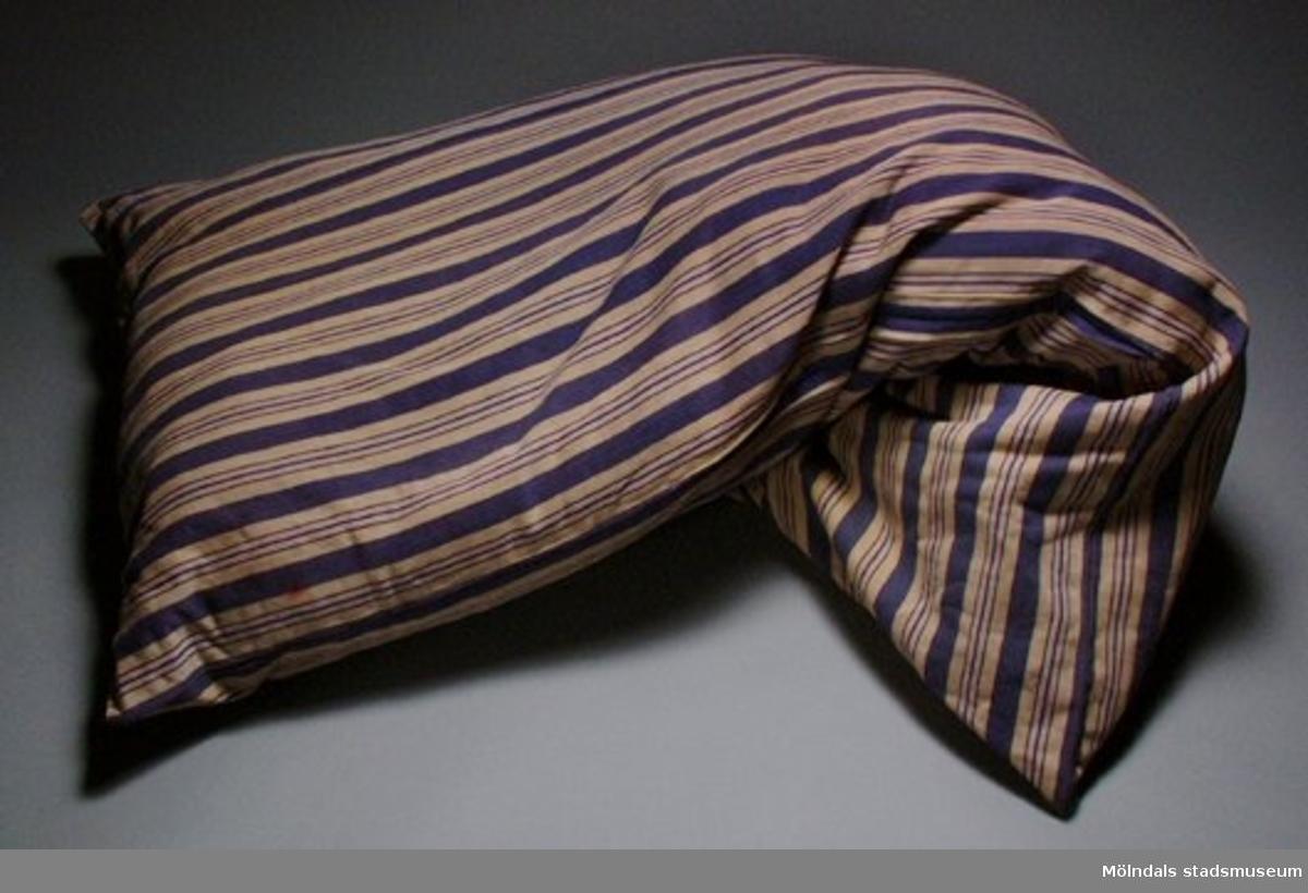 Madrassvar randigt i blått/beige/blekt rött. Troligen använt av släkten Zachrisson i Lindome.