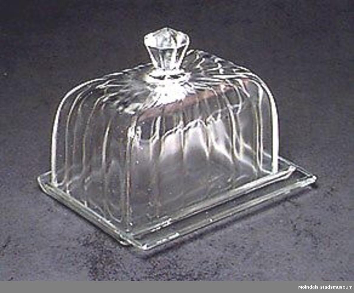 Kupa och bottenskiva av formpressat glas. Kupan kröns av en åttasidig knopp.