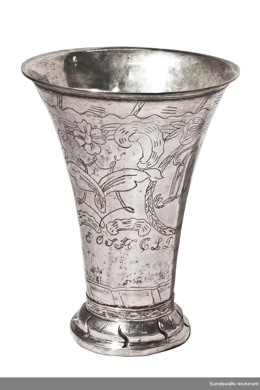 Bägare i silver, delvis förgylld. Konisk, insvängd. Kälad fot med svängda åsar och stämpeldekor. Runt foten och livet svisselerad dekor föreställande blommor och kartuscher med kungligt monogram, Gustaf IV Adolf, och initialerna 'ADW'. Senare graverade ägarinitialer är 'E.O.S.H.O.L D.'. I botten är '22lod' inristat. Stplr: C.P. Modin, Sundsvall 1806. Se även SuM 868:1-2, 905.  Litt.: Andrén, E., Svenskt silversmide 1520-1850, Nordisk Rotogravyr, Stockholm 1963, sid 524.