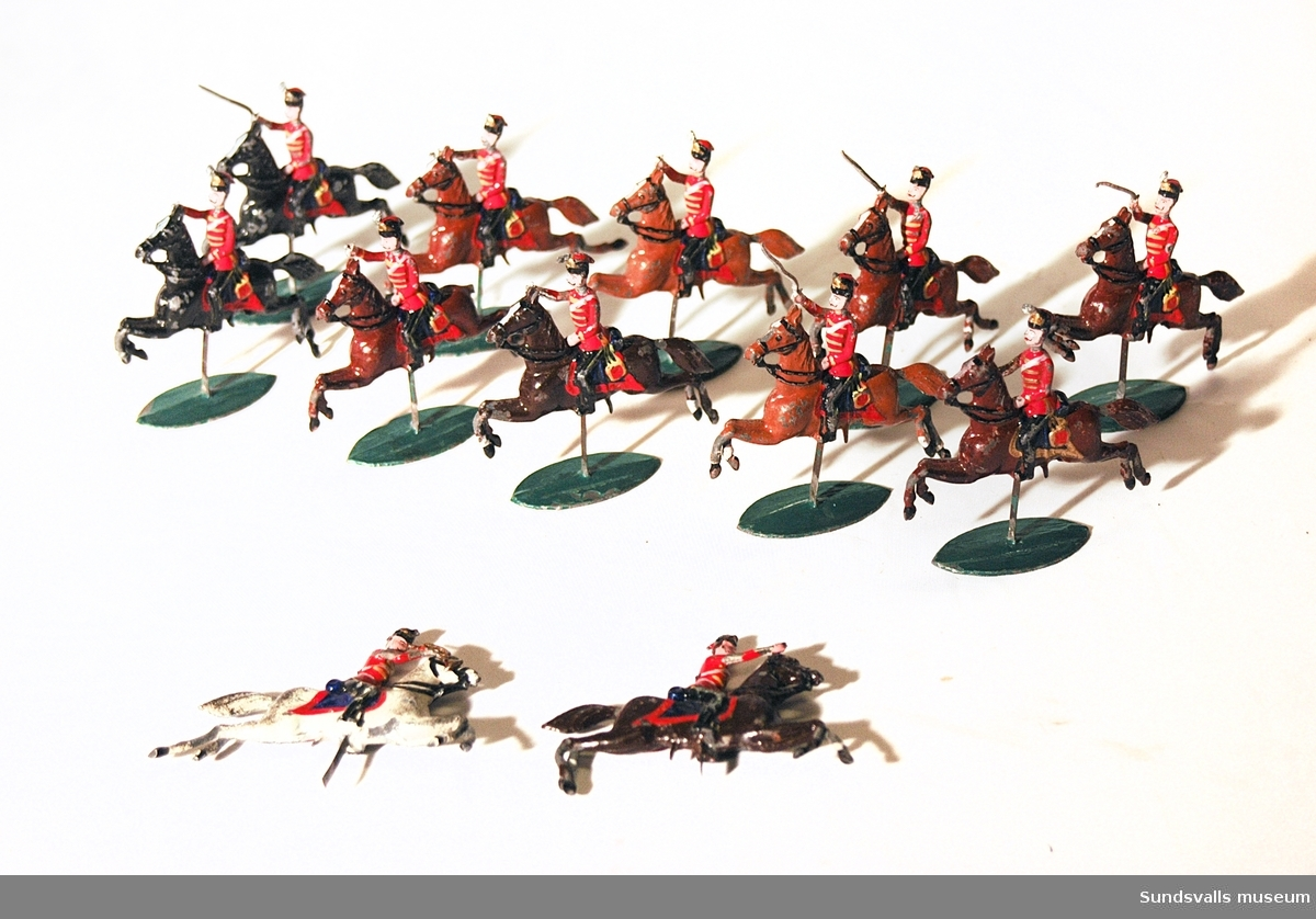SuM 2764:1-12, tennsoldater till häst. Alla ryttarna har röda jackor och svarta byxor med revärer. Av hästarna är en vit, två svarta, fyra ljusbruna och fem mörkbruna. Originalkartong i papp med tryckt text.