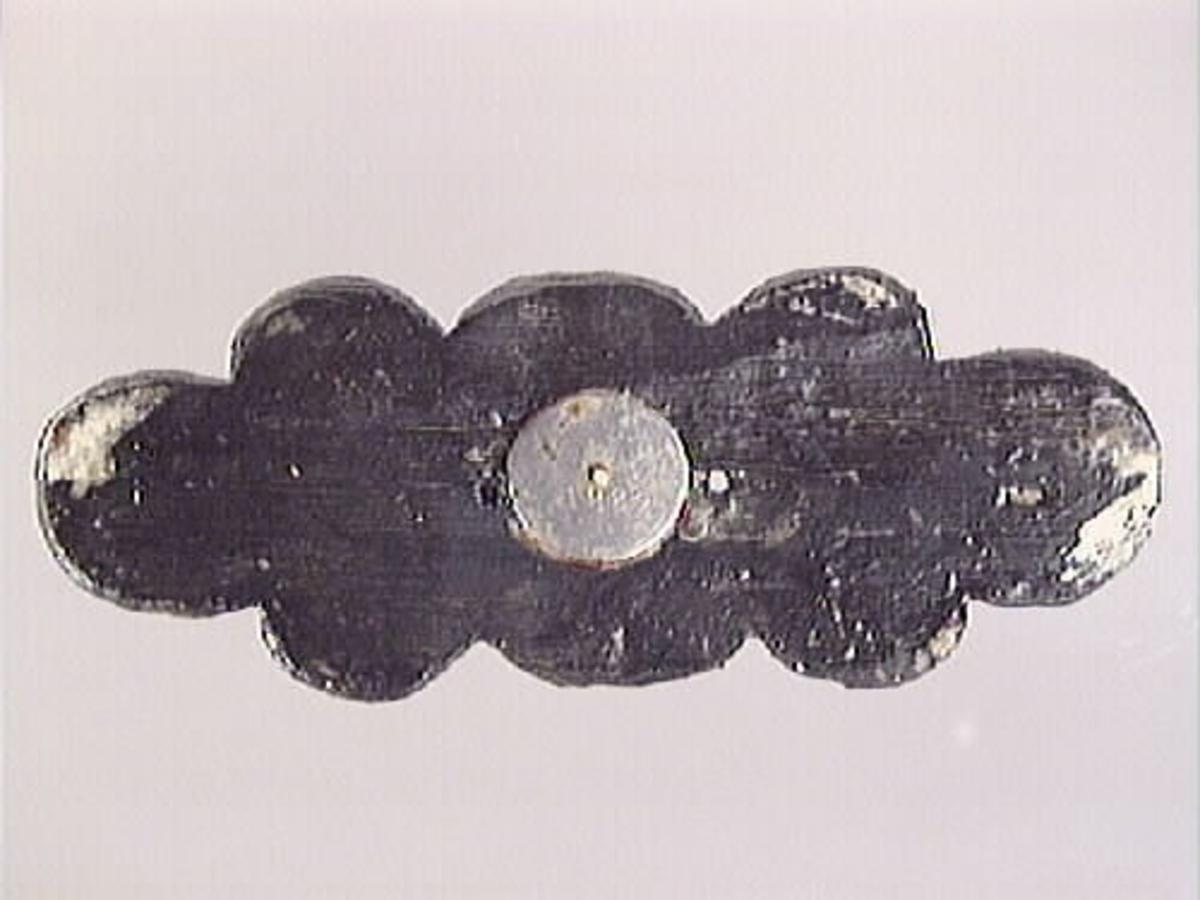Litet, profilerat ornament. Avlångt och symmetriskt, med ändarna formade som förtjockade, upprullade blad, liknande akantusblad. Vardera långsida pryds av ett segmentformat blad, som flankeras av kulliknande, något ovala förtjockningar. En liknande kula återfinns också i ornamentets mitt, flankerad av fyra symmetriskt ställda, halvrunda nedsänkningar. Spikhål på vardera sida om mittpartiets kula samt i ändarnas upprullade blad. Ornamentets baksida är slät. Ornamentet är välbevarat.  Text in English: Small, profiled ornament. Oval shaped and symmetrical. In the centre is a hemisphere, flanked by four symmetrically placed round cavities. On either side of the hemisphere is a small segmented leaf. Next to these, on the other end, are two half spheres with a thickened, rolled-up leaf in the middle. The latter resembles an acanthus leaf. The back of the ornament is smooth. Very well preserved.