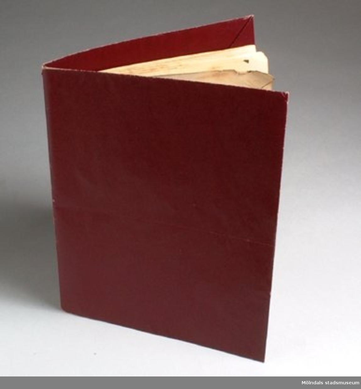 Pappersprov på s. k. väskpapper, vinrött. Har använts av Rut Larsson som bokomslag.