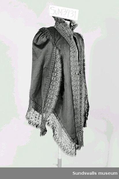 Cape (jacka) i svart ylle med spetsar och snörmakerier i svart. Knäppes med en klädd knapp, samt hake och hyska.