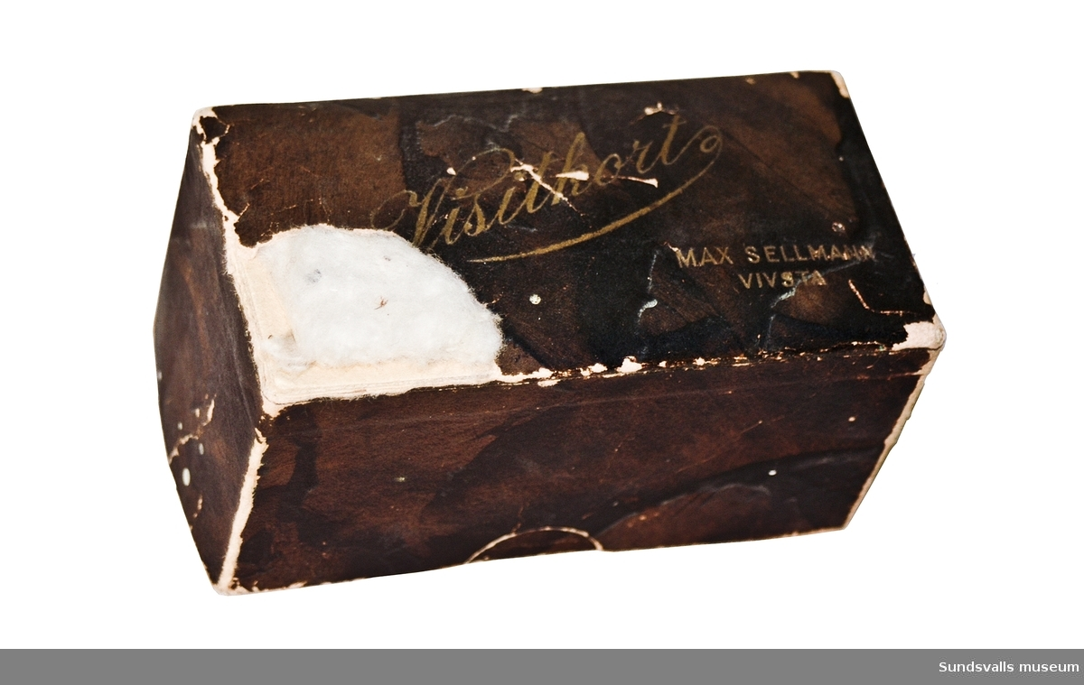 Brun pappersask för visitkort med texten 'Visitkort MAX SELLMAN VIVSTA' i guld på locket. Locket är vadderat.