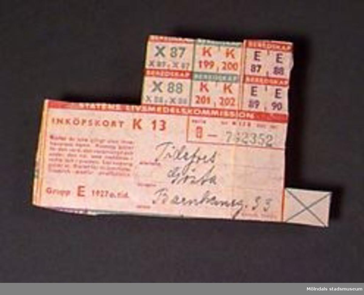 """Kort från """"STATENS LIVSMEDELSKOMMISSION"""", """"INKÖPSKORT K 13"""". Tio kuponger kvar. Tryckt huvudsakligen med röd färg på grågrönt papper. Kupong nr """"B - 762352""""."""