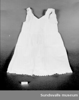 Vit ärmlös bomullsklänning med kort liv som är avskiljt från kjolen med två raksömmar. V-ringning fram och rakt avskuren bak. Hals, ärmhål och bröst har broderier med uddkant sytt med langett- och utdragssöm. Sytt veck längst ner på klänningen. Påsydd uddspets med langettsöm, blommönster i plattsöm och hål kantade med klumpsöm. Sprund i ryggen med fyra trådknappar och sydda öglor att knäppa med.