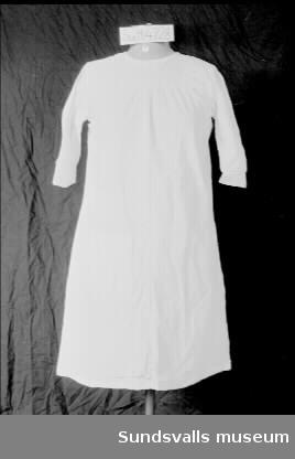 Särk i naturvit bomull med trekvartsärm. Rund hals. Tyget är avskuret i brösthöjd fram och bak. Knäppning i ryggen med fyra vita trådknappar. Påsydd ficka fram, fyrkantig med dubbelvikt tyg i övre kanten.