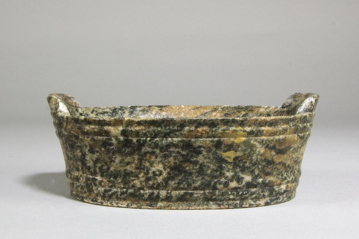 Smörask av sten. Oval form med höga, svagt utåtstående, sidor och med två öron på kortsidorna. Med profilerade bårder.