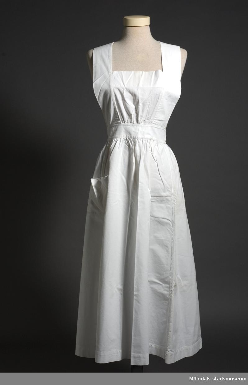 """Förkläde av vitt lakansväv. Band som knyts i kors i linningen på ryggen. En ficka på höger sida. Påsytt märke """"SÖS 591"""" och handskrivna initialer """"EH"""" på kjoldelens underkant."""