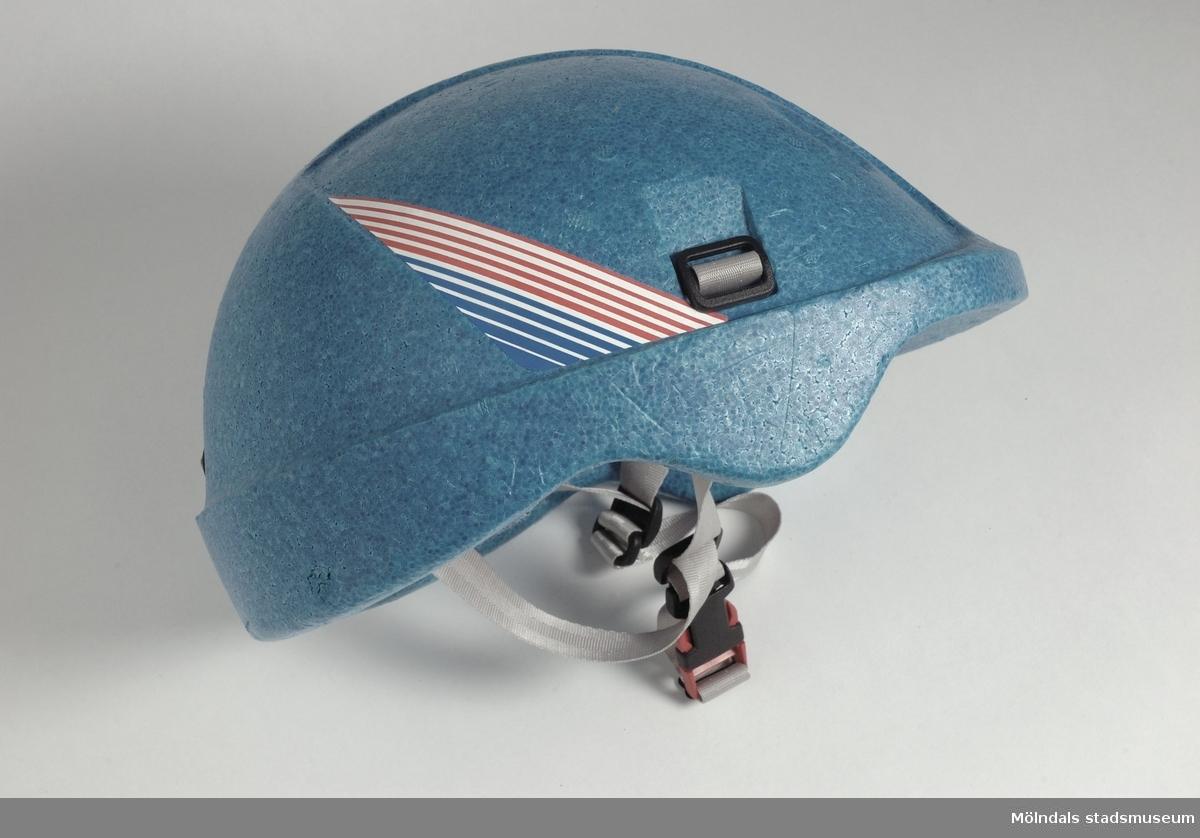 """Blå frigolithjälm med gråa remmar runt hakan.Efter rekommendationer och att ha kört omkull med cykeln, börjat använda hjälm. Cyklat till och från jobbet och använt hjälmarna tillsammans med sonen.På 1980-talet accepterade man vad som fanns att köpa, även om hjälmens utseende inte var snyggt.Text på insidan av hjälmen: """"Utformad enligt konsumentverkets regler för säkerhet och funktion för cykelhjälmar"""""""
