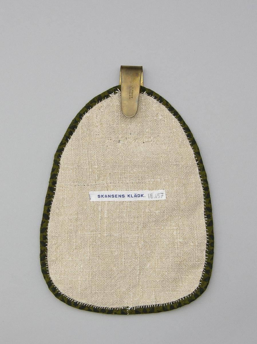 Kjolsäck till kvinnodräkt från Ovansjö socken, Gästrikland. Modell med avskuret framstycke. Tillverkad av mörkblått ylletyg, kläde, med applikationer av rött, grönt och gult kläde, fastsydda med langettsöm med vit lintråd. Motiv: hjärta med slingor och bladformer. Även flätsöm har använts, dels till att sy fast en applikation, dels till två böjda linjer. Kantning upptill med rött kläde. Kantning runtom med fabriksvävt bomullstyg med tryckt mönster i mörkgrönt och svart. Framstycket fodrat med grovt vitt linnetyg, tuskaft, samma tyg har använts till bakstycke. Överstycke av mörkblått kläde med beslag av mässing, fast hake. Beslaget är hjärtformat och har genombruten stansad dekor, tre korsblommor.