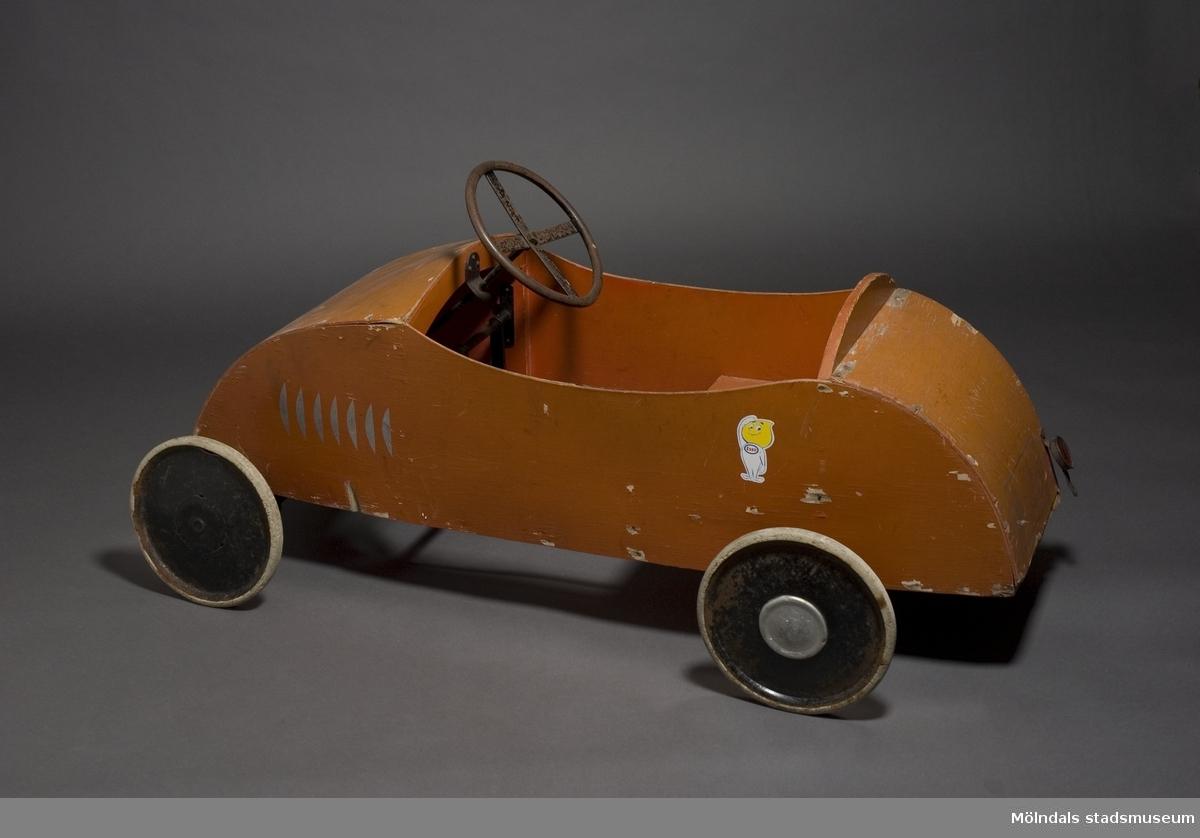 Trampbil av trä. Målad i rött och grönt. Hjul av gummi. Baktill står registreringsnummer A38.När man sitter i bilen kan man ta sig fram genom att trampa runt pedalerna och styra med ratten. Trampbilen har brukats först av Alf Olofsson och senare av sonen Jonas och barn-barnet Lucas.