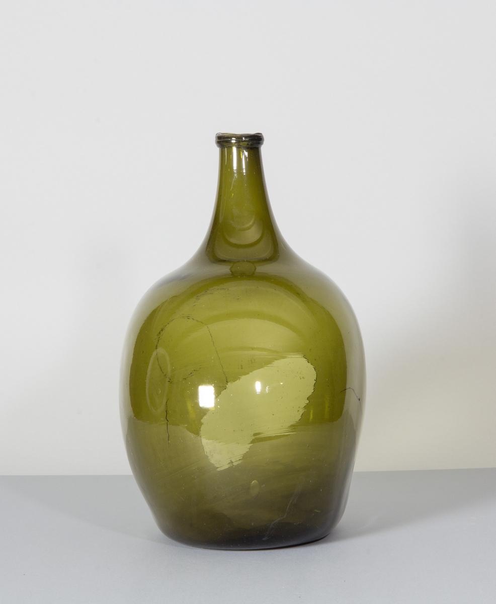 Flaska i glas, grön till färgen. Rundade sidor, hals med halsring, platt botten.