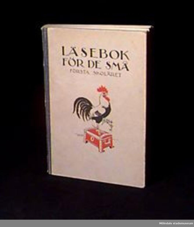 """""""Läsebok för de små"""" för första skolåret. Grått omslag med teckning  i svart och rött av tupp på en kassakista. Blå textilrygg. På insidan av omslaget tryckt etikett med text: """"Denna bok tillhör"""" och skrivet med bläck: """"Rune Olsson""""."""