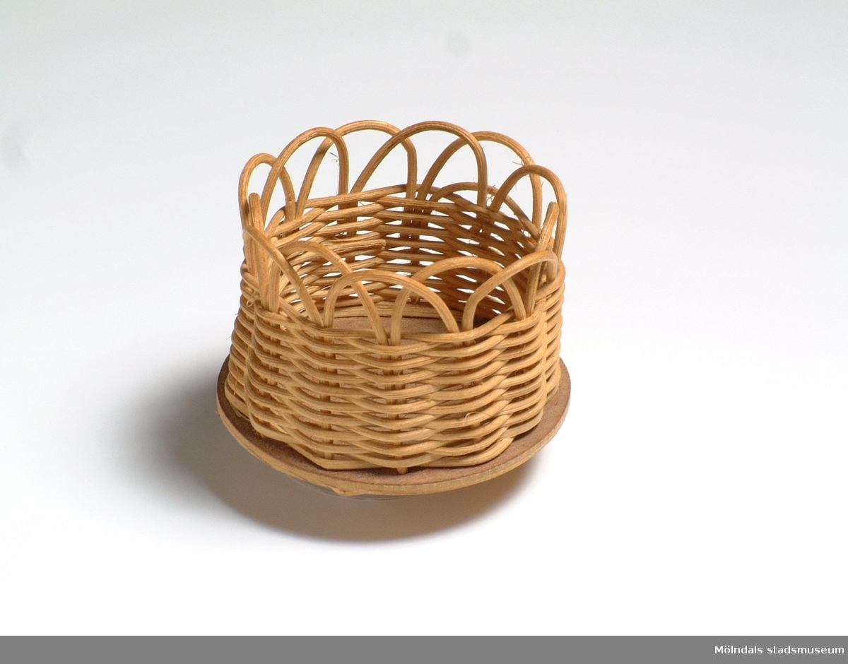 """Flaskkorg, tillverkad av en bottenplatta av en plywood och fästad i denna, själva korgen, flätad av en typ av rotting. Korgen är upptill avslutad i bågar. I botten står skrivit Karin Pettersson Klass V BGivaren tillverkade denna flaskkorg i klass 5 i Brattåsskolan, Kållered. Utöver vanlig syslöjd, hade eleverna sk. """"småslöjd"""", där denna tillverkades. Användes för att sätta öl och läskflaskor i, när man satte fram dem på bordet."""