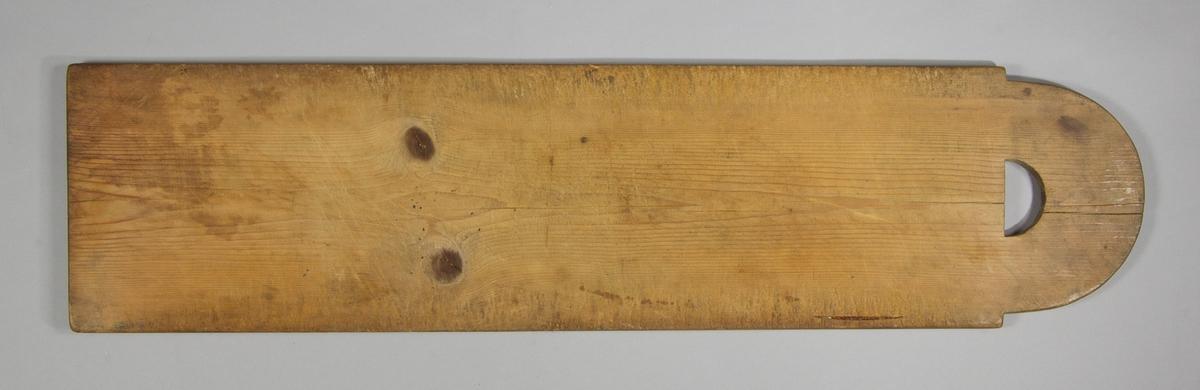 Skärbräda av furu. Rektangulär med halvcirkelformad kortsida med halvmåneformat hål för upphängning.