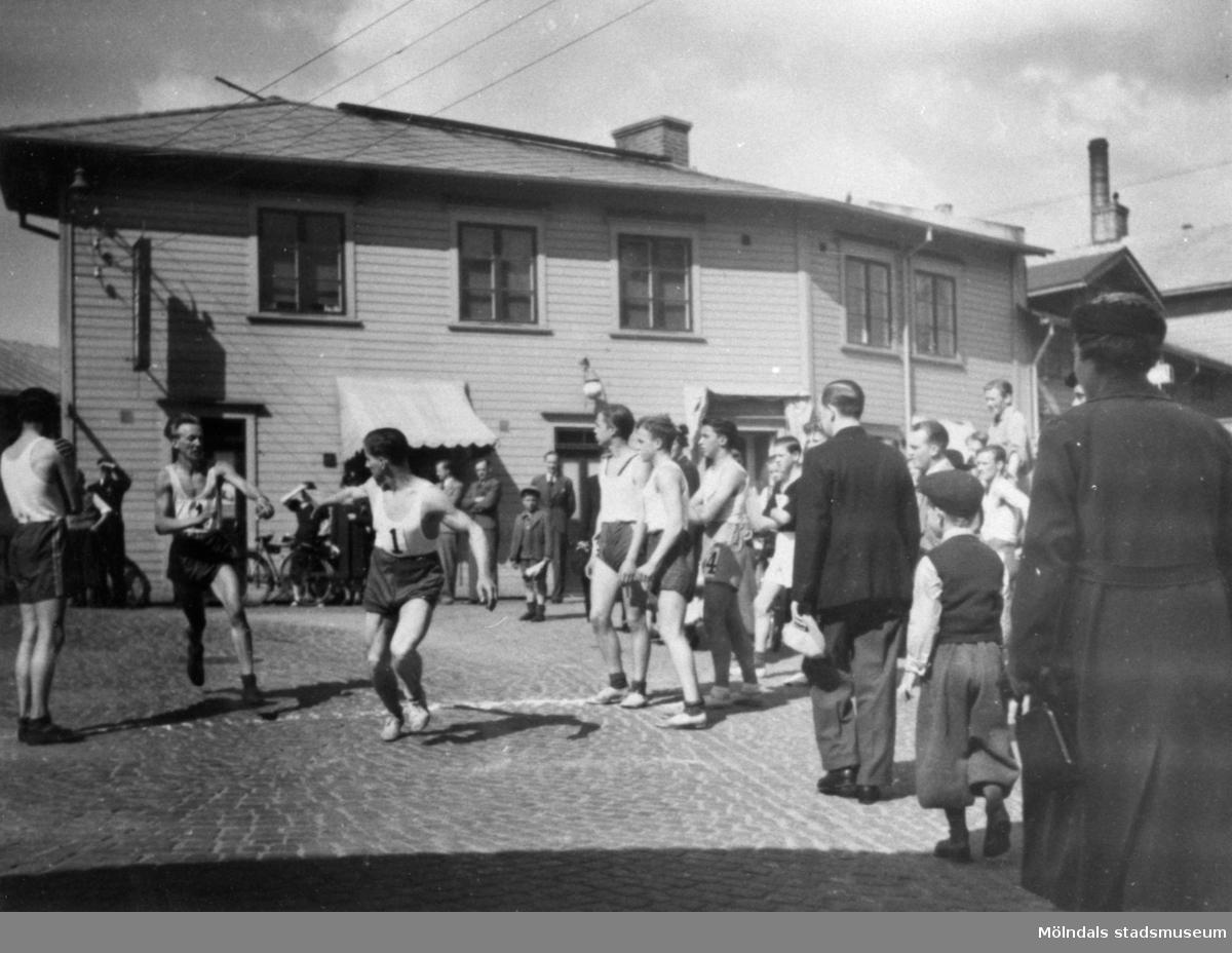 """MSK (Mölndals stafettklubb). Stafett """"Mölndal runt"""" på  Forsåkersgatan/Götaforsliden 1938. Forsells Cigarraffär i bakgrunden."""