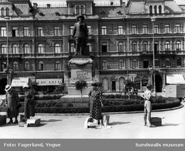 """Torghandel på Stora Torget i Sundsvall. I bakgrunden Harald Sörensen-Ringis staty av Gustav II Adolf och butikerna i kv Nyttan.  I den s k """"Bondraden"""" fick man stå närmast runt Gustav Adolfs statyn. Man behövde där inget tillstånd för utöva torghandel."""