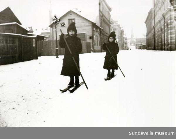 Två barn åker skidor på gata