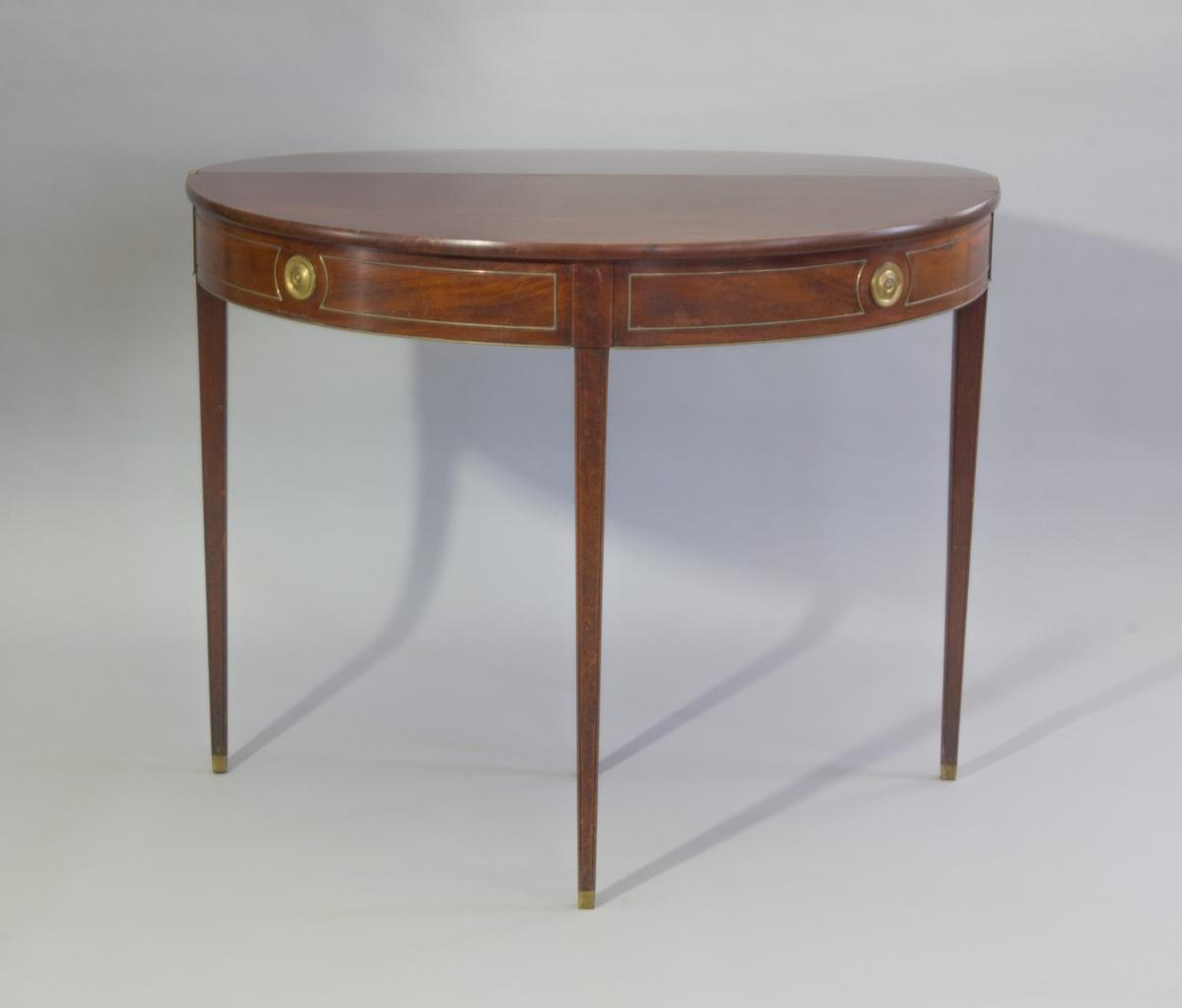 Bord, spelbord, av mahogny med rund fällbar skiva. Tre fasta ben, ett fjärde som är utdragbart. Beslag och lister av mässing.