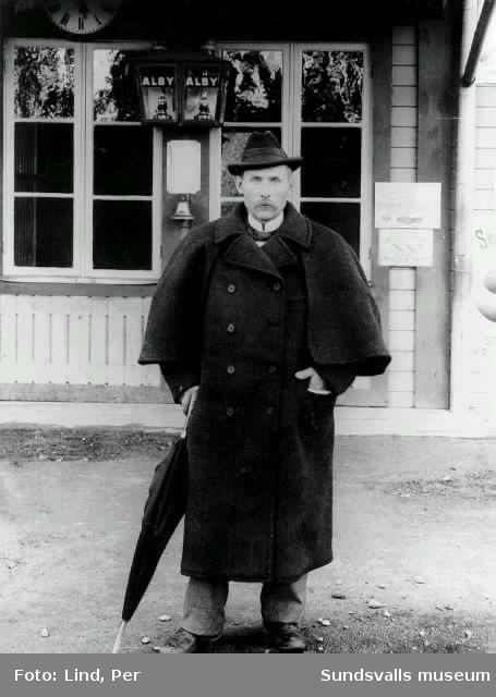 Alby 1898. Man med paraply vid stationsbyggnaden.