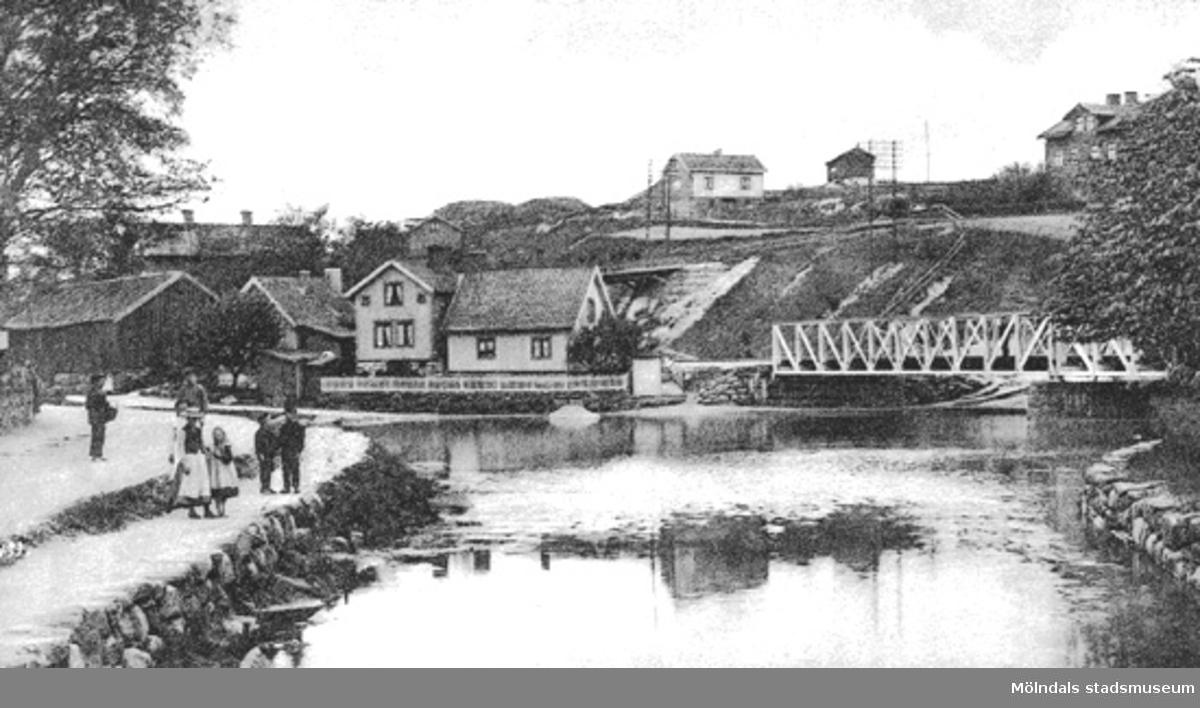 """Foto som vykort: """"Parti från Mölndal"""" som visar övre delen av Mölndalsån, cirka 1900-1907. Utsikt utmed Pixbovägen och järnvägsbron mot Ormås och Stensjöbacke."""