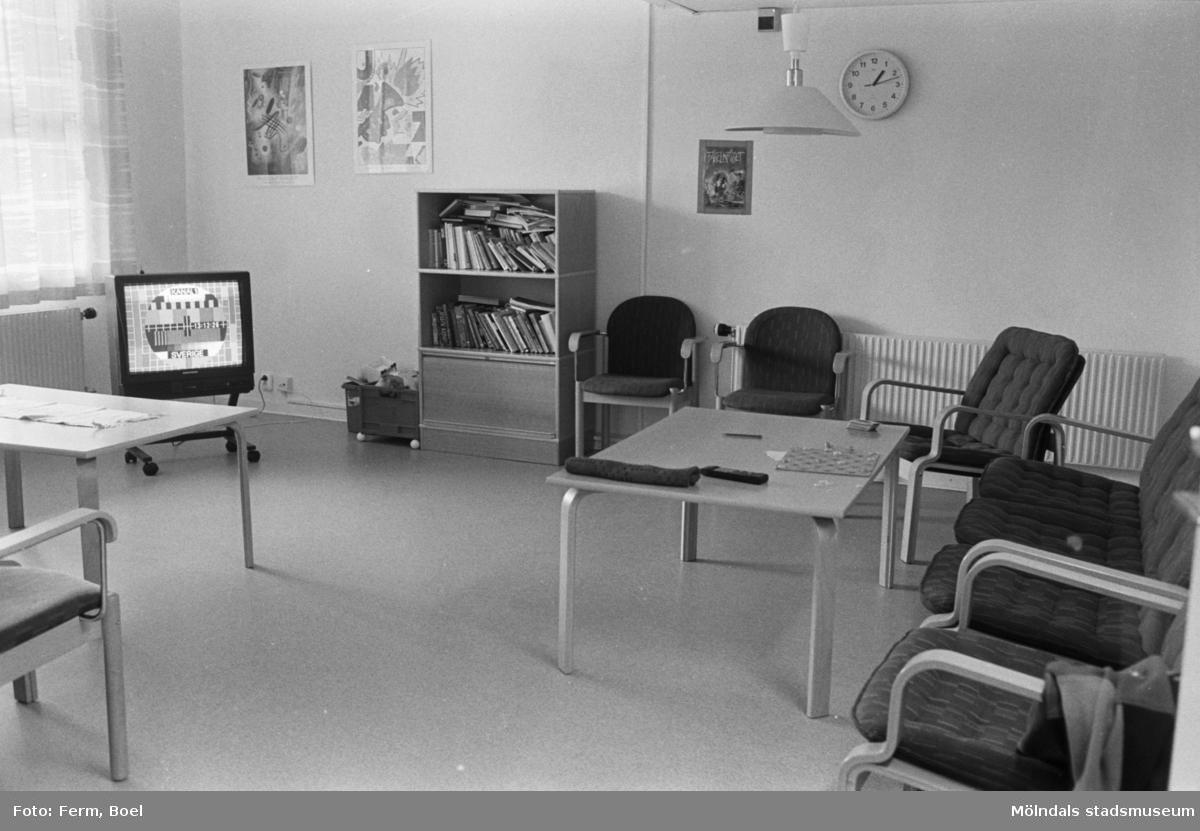 Dokumentation av Sagåsens flyktingförläggning 1992. Ett möblerat allrum med tv, bokskåp, bord och fåtöljer.