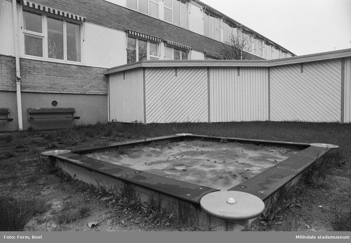 Dokumentation av Sagåsens flyktingförläggning 1992. Exteriör vy på sandlåda, insynsskydd samt byggnad.
