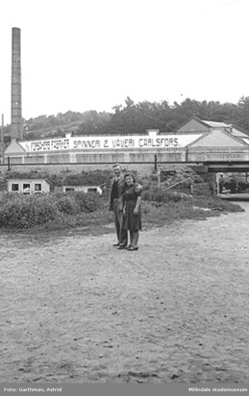 Viktor Karlsson (morfar till givaren Alf Garthman) håller om en okänd kvinna utanför övre av (Forsåkers fabriker) Spinneri & Väveri Carlsfors fabriker, 1940-tal. I bakgrunden syns banvallen (Boråsbanan) som delar fabriken och bostäderna vid Kvarnfallet 31 i Mölndals kvarnby.