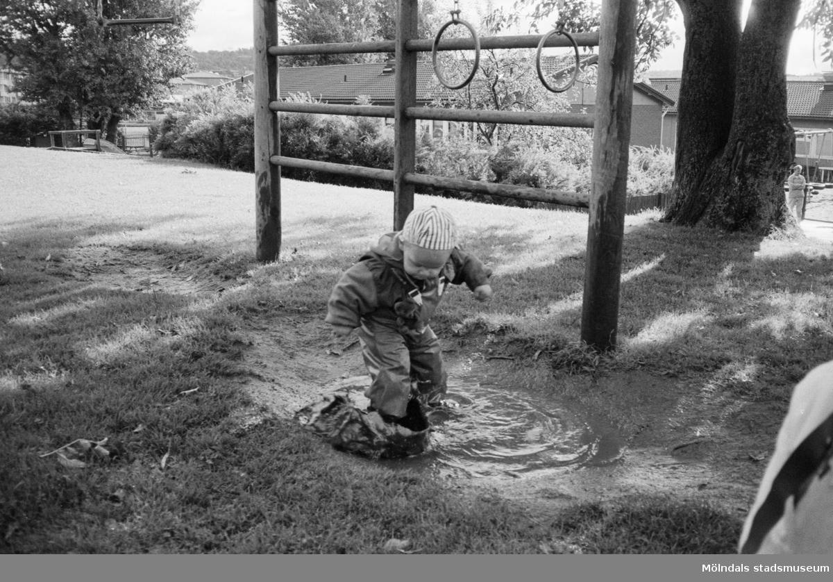 En liten pojke klädd i regnkläder står och hoppar i en vattenpöl. I bakgrunden ser man en klätterställning bredvid ett träd. Katrinebergs daghem, 1992.