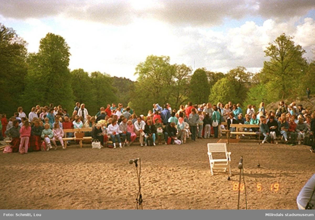 Människor som ser på någon form av uppträdande. De sitter i bänkar på Gunnebo slotts framsida.